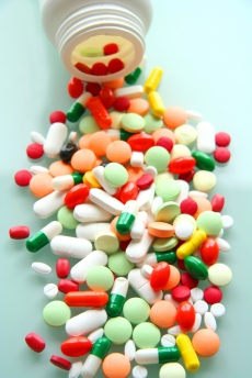 colored pills spilling out of a bottle