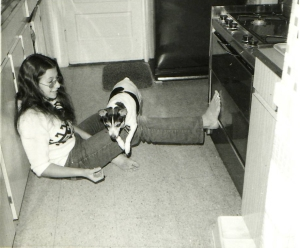 girl sitting on floor with dog jumping over her leg
