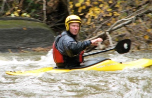 man paddling a yellow kayak in white water