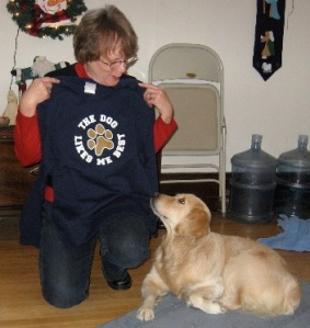 woman holding t shirt that says the dog likes me best