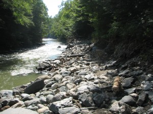 road along river washed out to reveal large stones