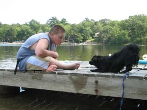 boy with a small black dog bowing at him