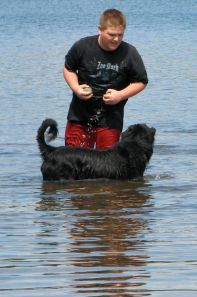 boy playing with black dog in a pond