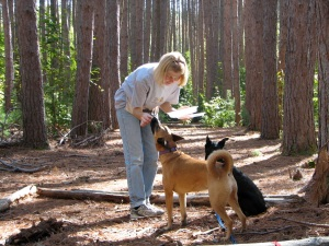 women giving treats to two dogs while outside in the forest