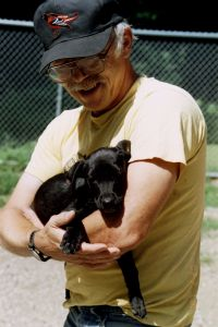 small black dog being held by a man at an animal shelter