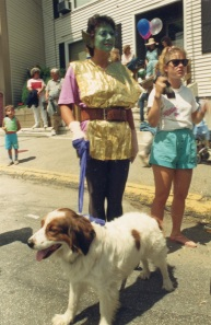 woman with elf make up on and  holding a dog on a leash