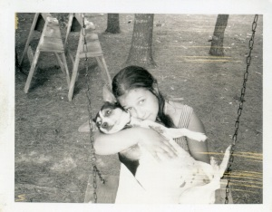 old photo of girl with fox terrier cradled in her lap