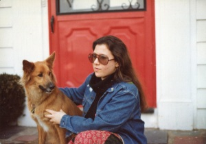 young woman wearing sunglasses sitting on a stoop with a dog