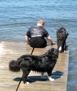 boy sitting on pier with 2 dogs looking at the water